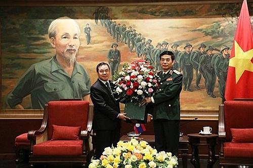 ឯកអគ្គរដ្ឋទូតវិសាមញ្ញ និងពេញសមត្ថភាពប្រទេសឡាវប្រចាំនៅប្រទេសវៀតណាម លោក Sengphet Houngbuongnuang ជូនផ្កាលោករដ្ឋមន្រ្តីក្រសួងការពារប្រទេស Phan Van Giang។ (រូបថត៖ QĐND)
