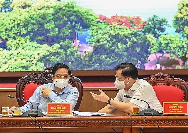 លេខាគណៈកម្មាធិការបក្សទីក្រុងហាណូយលោក Dinh Tien Dung (ខាងស្ដាំ) ផ្លាស់ប្ដូរមតិជាមួយលោកនាយករដ្ឋមន្រ្តី Pham Minh Chinh។ (រូបថត៖ cand.com.vn)